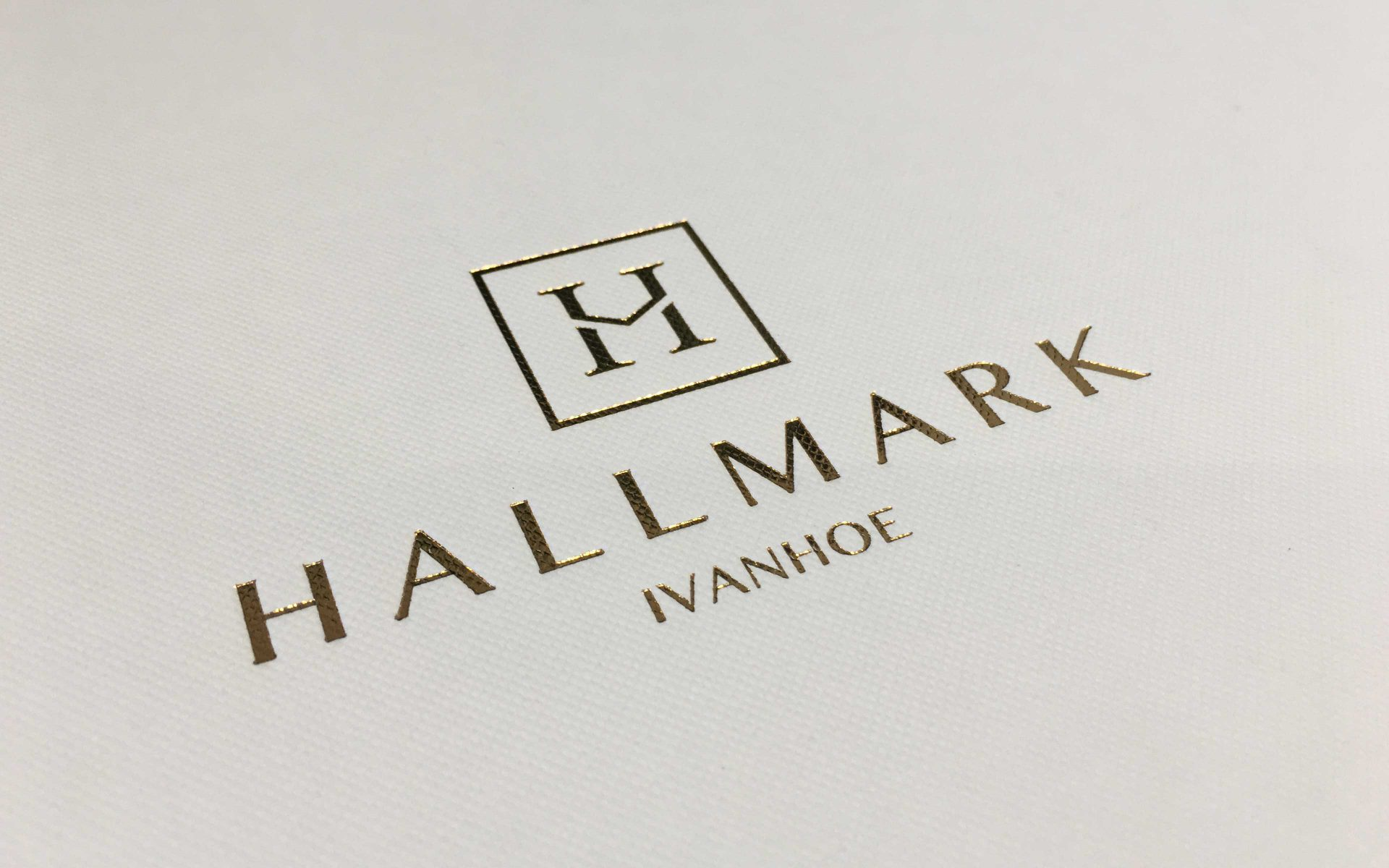 Hallmark gold embossed logo on white cardboard by Differ