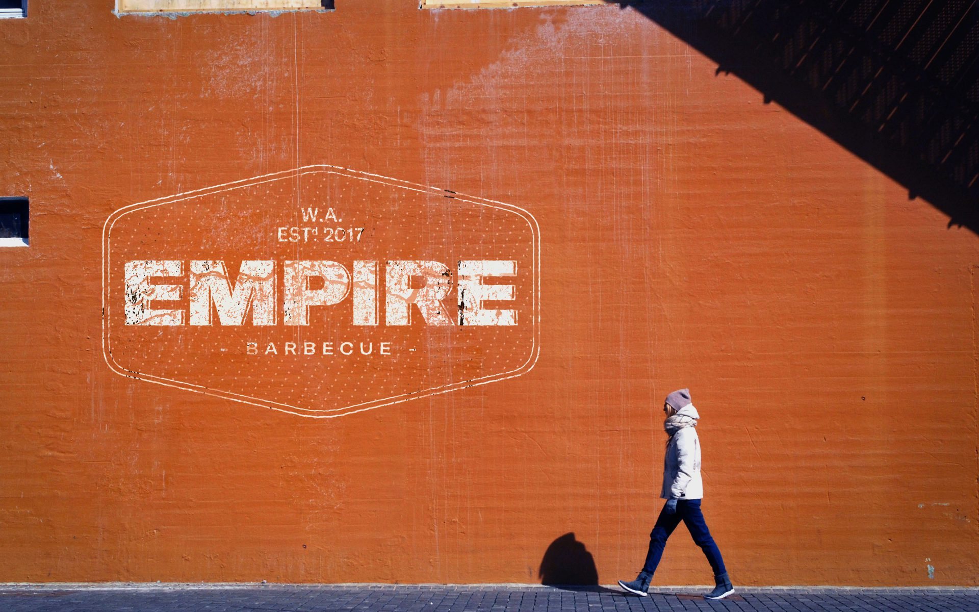 Empire BBQ brand logo on red wall